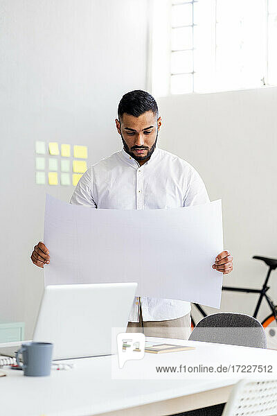 Male entrepreneur holding business plan by laptop while standing at office