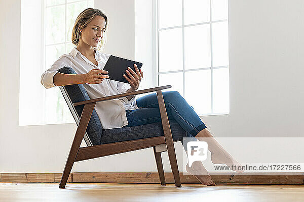 Woman sitting on armchair and looking at digital tablet