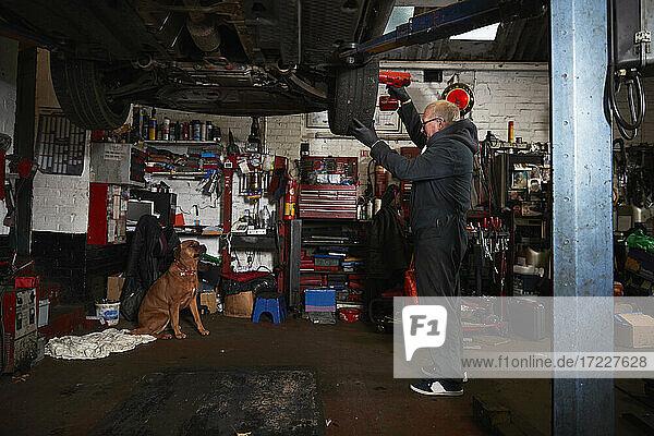 Senior male mechanic replacing tire in garage