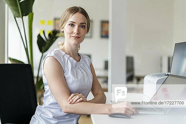 Weibliche Fachkraft sitzt vor einem Laptop im Büro