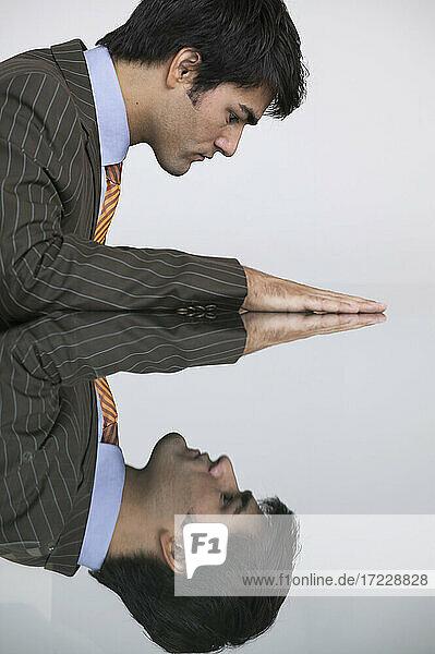 Reflexion von Geschäftsmann in Konferenzraum Tabelle