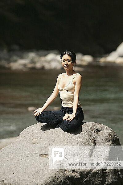 Porträt schöne junge Frau meditiert in Lotus-Pose auf sonnigen Felsen