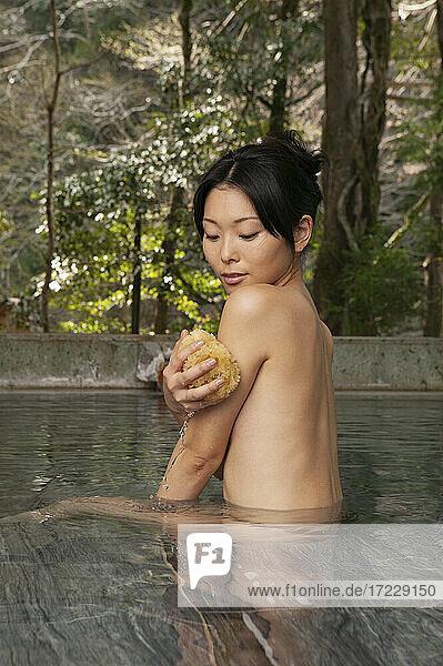 Nackte junge Frau mit Luffa im ruhigen Onsen-Pool