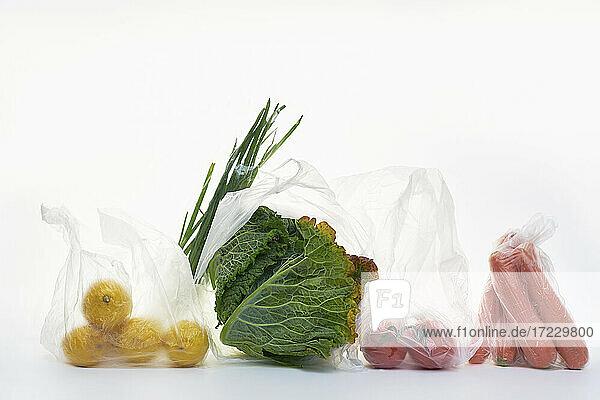 Stillleben mit Lebensmitteln in Plastiktüten auf weißem Hintergrund