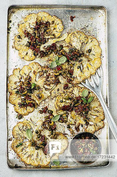 Blumenkohlsteaks mit Olivensalsa auf Ofenblech