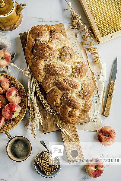 Hausgemachtes Challah-Brot (jüdische Küche) serviert mit Honig und Pfirsichen