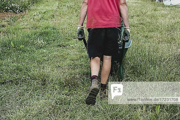 Rückansicht eines Landwirts  der mit einer Schubkarre über ein Feld fährt.