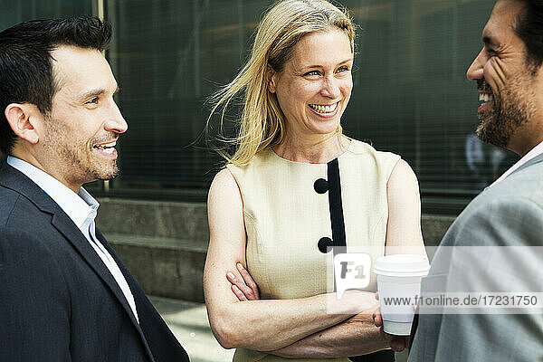 Businesswoman and two businessman standing outdoors  chatting and smiling.