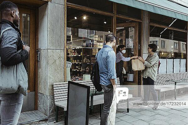Weiblicher Kunde  der ein Lebensmittelpaket von der Verkäuferin im Feinkostladen abholt  während COVID-19