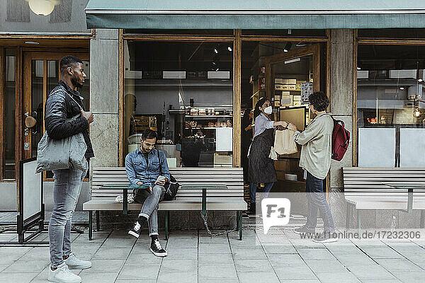 Kunden halten soziale Distanz beim Abholen der Bestellung im Feinkostladen während der Pandemie