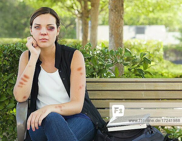 Sad bruised and battered young woman sitting on bench outside at a park