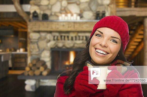 Smiling mixed race girl enjoying warm fireplace and holding mug of cocoa or hot tea