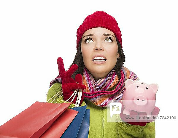 Stressed mixed-race woman wearing winter clothing looking up holding shopping bags and piggybank isolated on white background