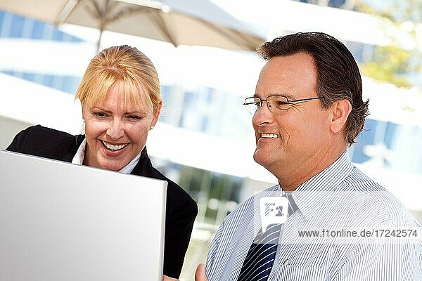 Handsome businessman laughs while working on the laptop with attractive female colleague outdoors