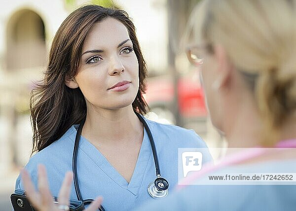 Two young adult professional female doctors or nurses talking outside