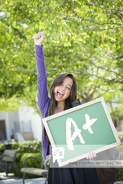 Excited mixed race female student holding a chalkboard with A+ written on it