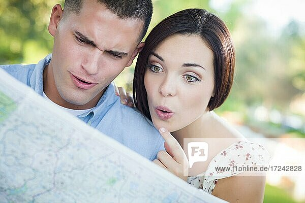 Happy mixed-race couple looking over A map outside together