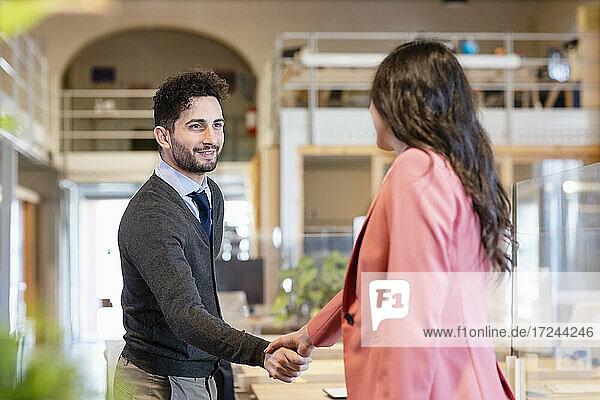 Junger Geschäftsmann schüttelt Hände mit Unternehmerin in Coworking-Büro