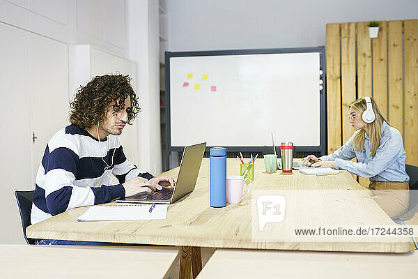Lockenhaariger Geschäftsmann mit Laptop am Konferenztisch im Büro