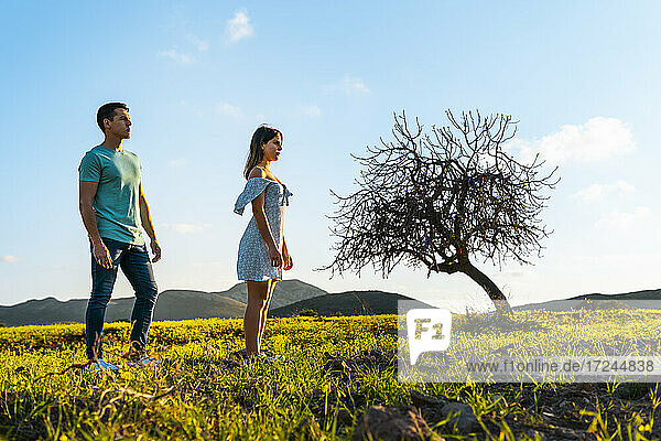 Young woman standing at distant with man on grass