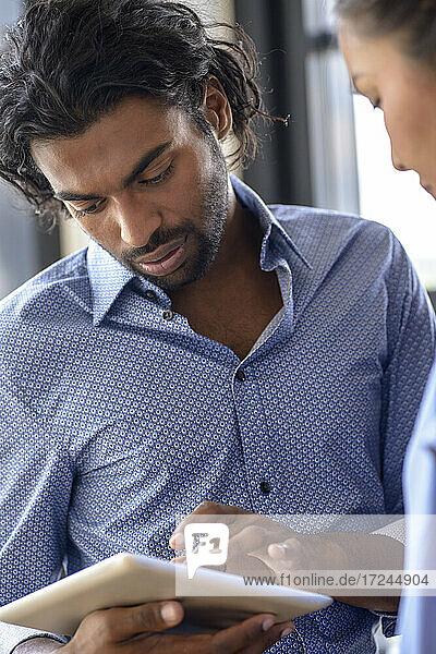 Männlicher Student  der ein digitales Tablet von einer Kollegin in der Universität benutzt