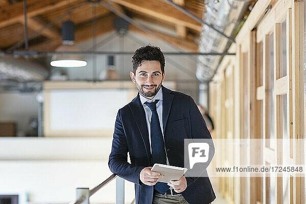 Gutaussehender Mann mit digitalem Tablet  der sich auf ein Geländer im Büroflur stützt