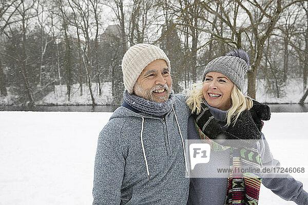 Senior couple wearing warm clothing smiling at park