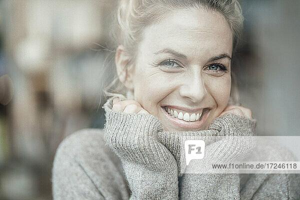 Mittlere erwachsene Frau im Pullover lächelnd mit Hand am Kinn