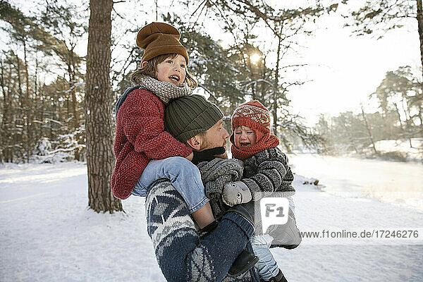 Vater  der einen Jungen auf der Schulter trägt und seinen weinenden Sohn im Winter betrachtet