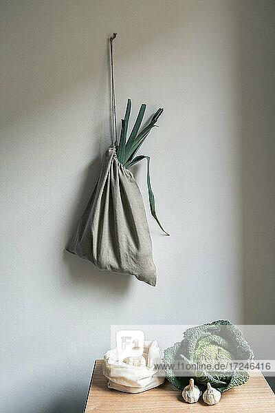 Gemüse auf dem Tisch und Leinensack an der weißen Wand Gemüse auf dem Tisch und Leinensack an der weißen Wand