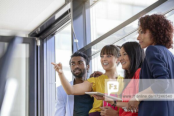 Geschäftsfrau zeigt auf Kollegen im Büro