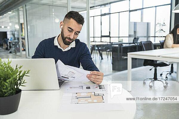 Männlicher Fachmann  der ein Dokument in einem Coworking-Büro liest