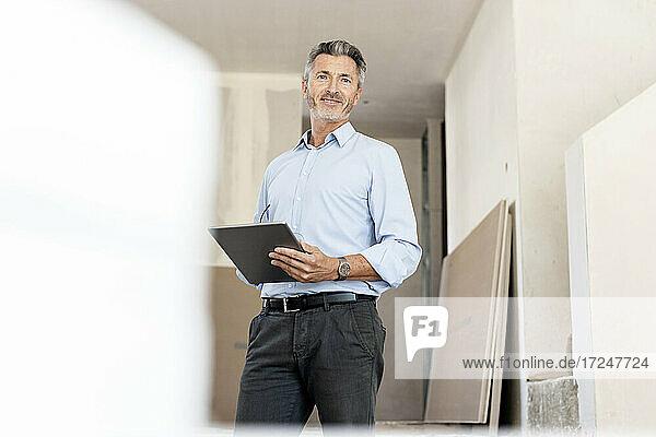 Männlicher Fachmann mit digitalem Tablet auf einer Baustelle