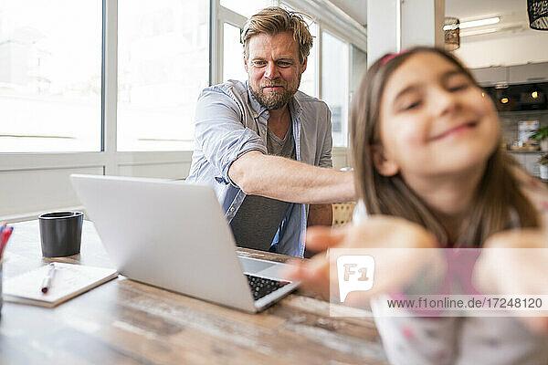Geschäftsmann schaut auf einen Laptop  während er neben seiner spielenden Tochter zu Hause sitzt