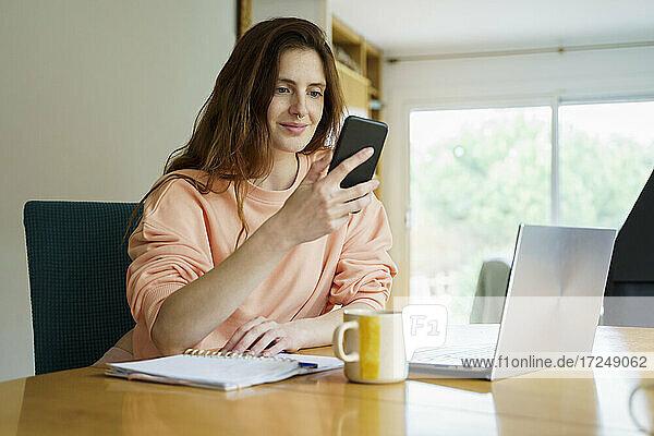 Frau benutzt Smartphone  während sie mit Laptop und Kaffeetasse am Tisch sitzt