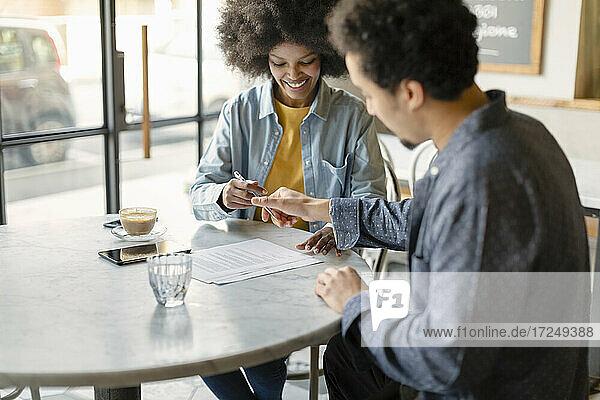 Ein männlicher Kunde und eine Geschäftsfrau unterzeichnen einen Vertrag  während sie im Cafe sitzen