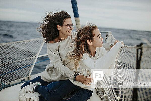 Mutter und Tochter betrachten die Aussicht während der Fahrt mit einem Segelboot auf dem Meer im Urlaub Mutter und Tochter betrachten die Aussicht während der Fahrt mit einem Segelboot auf dem Meer im Urlaub