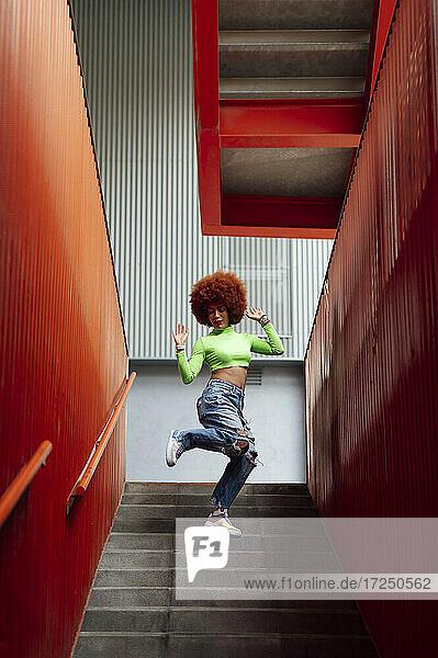 Cheerful woman dancing on staircase