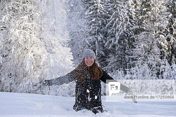 Happy woman with arms outstretched sitting on snow during vacations