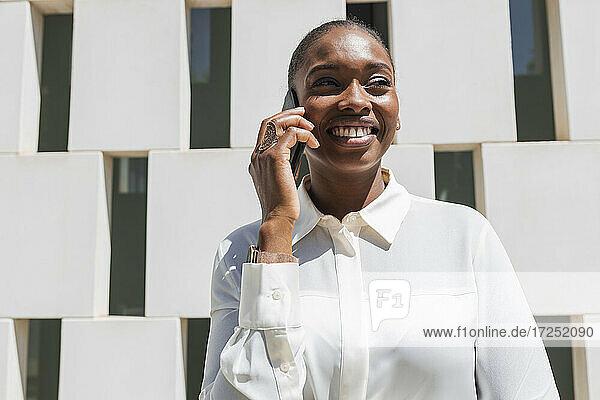 Weibliche Geschäftsfrau lächelt  während sie mit einem Mobiltelefon spricht