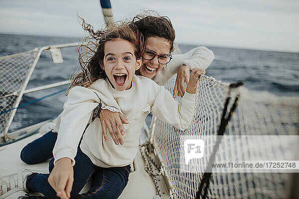 Lachende Mutter mit aufgeregter Tochter auf Segelboot im Urlaub Lachende Mutter mit aufgeregter Tochter auf Segelboot im Urlaub