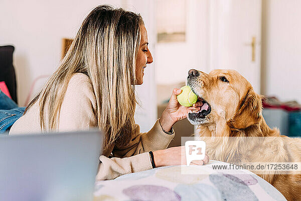 Italy  Young woman playing with dog at home