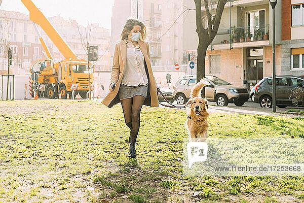 Italy  Woman with dog walking in urban setting