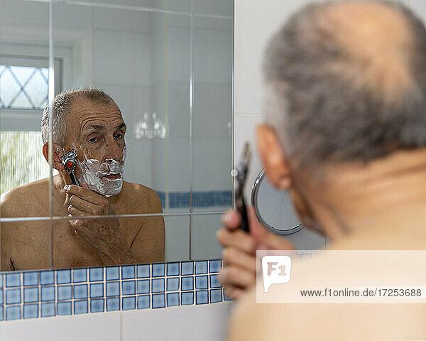 UK  East Sussex  Senior man shaving in front of bathroom mirror