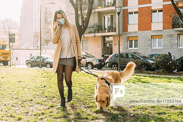 Italy  Young woman and dog walking on grass