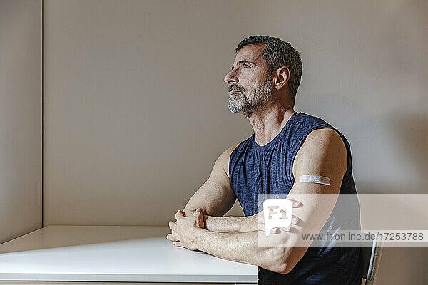 France  Man with bandage on arm sitting at table
