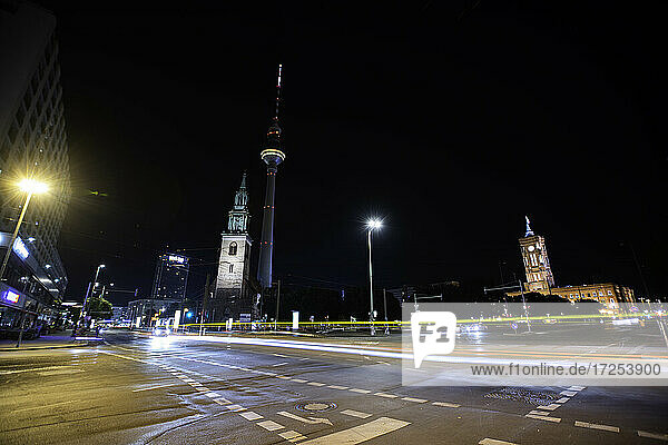 Low angle view of church and Fernsehturm Berlin with traffic on street in foreground at night