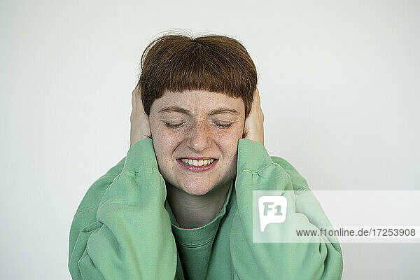 Close-up of stressed woman with eyes closed covering ears with her hands