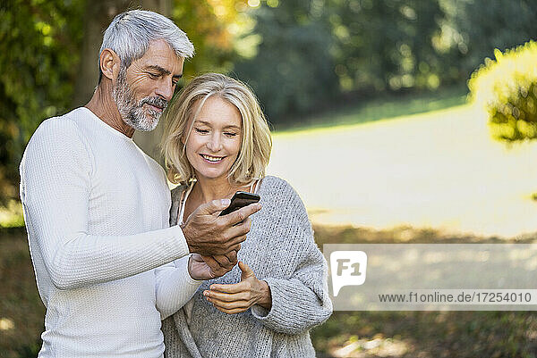 Smiling mature couple using smartphone in backyard