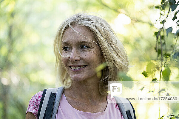 Portrait of smiling mature woman with backpack in forest